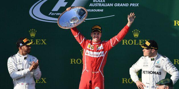 Ferrari's German driver Sebastian Vettel (C) celebrates on the podium with Mercedes' British driver Lewis...