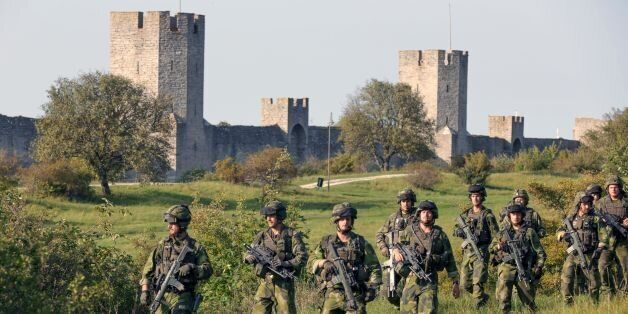 A squad from Skaraborg Armoured Regiment patrol outside Visby's 13th century city wall in Sweden on September...