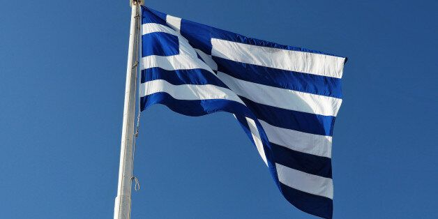 The blue and white official flag of Greece against blue