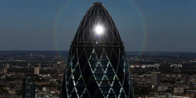 The sun reflects off the top of 30 St Mary Axe, also known as The Gherkin, in London, U.K., on Tuesday,...