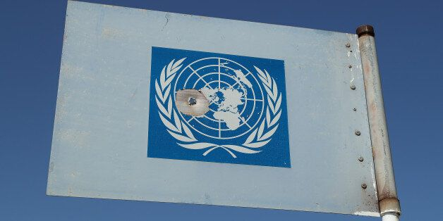DUCZE, CYPRUS - MARCH 06: A United Nations metal flag with a bullet hole in it stands on a U.N. peacekeepers'...