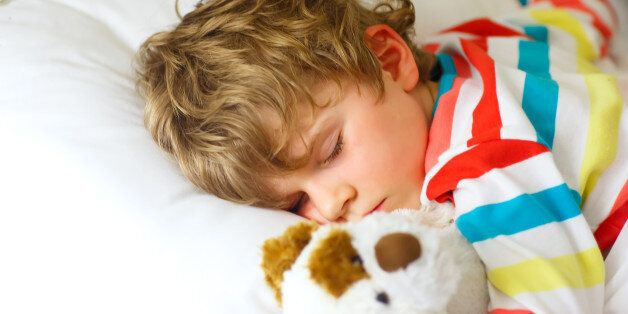 Adorable little blond kid boy in colorful nightwear clothes sleeping and dreaming in his white bed with...