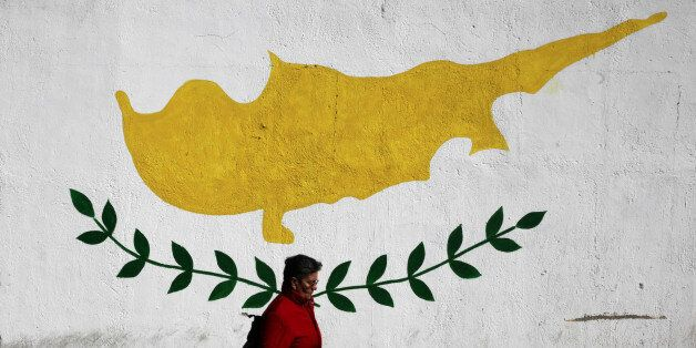 A woman walks in front of Cypriot flag painted on a wall in capital Nicosia, Cyprus February 22, 2017....