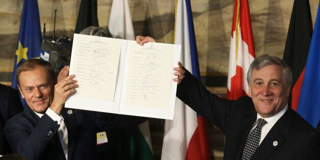 European Council President Donald Tusk (L) and European Parliament President Antonio Tajani hold up a...