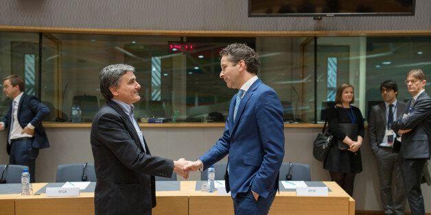 Euclid Tsakalotos, Greece's finance minister, left, shakes hands with Jeroen Dijsselbloem, Dutch finance...