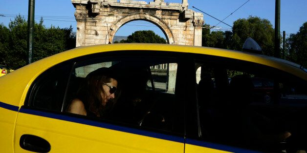 A woman rides in a taxi past an ancient site in Athens May 5, 2012. A ban on campaigning took effect...