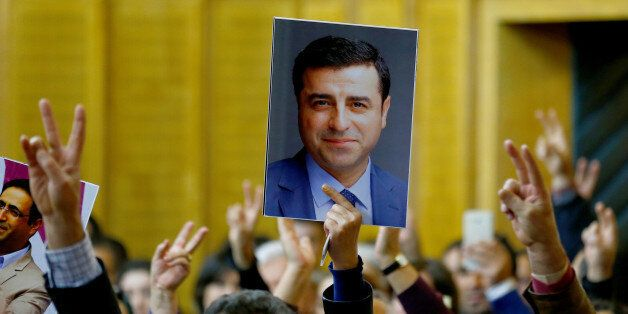 A supporter holds a portrait of Selahattin Demirtas, detained leader of Turkey's pro-Kurdish opposition...