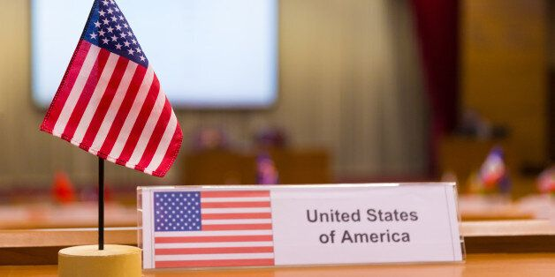 United States of America's small flag on meeting table, with blurred meeting room