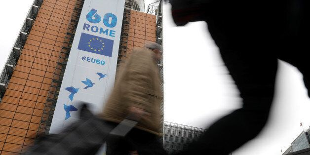 People walk past the European Commission headquarters in Brussels on which is displayed a banner celebrating...