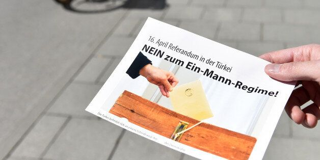 A man holds a flyer with the inscription 'April 16 - referendum in Turkey - No to the one-man regime!'...
