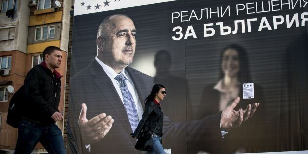 Bulgarians walk past an election poster bearing a portrait of the head of the centre-right GERB party...
