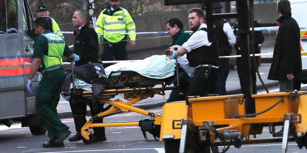 Members of the emergency services take an injured person away on a stretcher after an incident on Westminster...