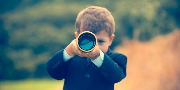 Young boy in a business suit with telescope. Small child wearing a full suit and holding a telescope....