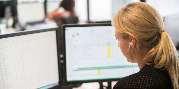 Businesswoman with headset at workstation looking at