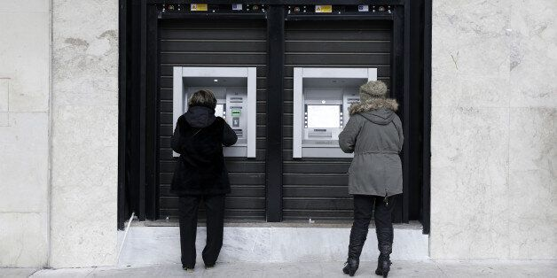 Customers withdraw cash from automated teller machines (ATM) operated by the National Bank of Greece...