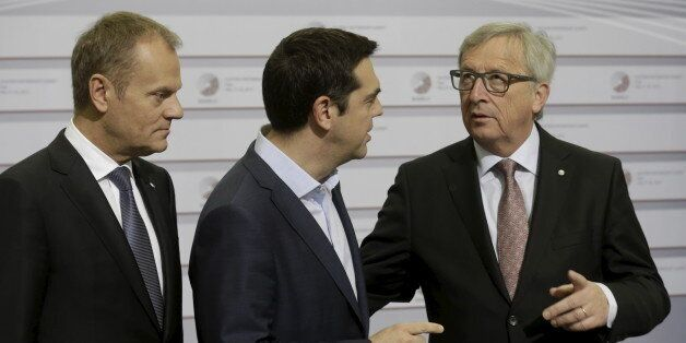European Council President Donald Tusk (L) looks on as Greece's Prime Minister Alexis Tsipras (C) speaks...