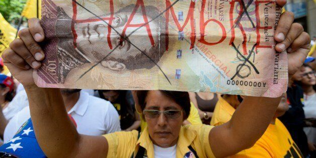 An activist of Venezuela's opposition holds a fake bill reading 'Hunger' during a demonstration in Caracas...