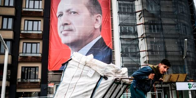A man pulls a cart in front of a huge portrait of Turkish President Recep Tayyip Erdogan on Taksim Square...