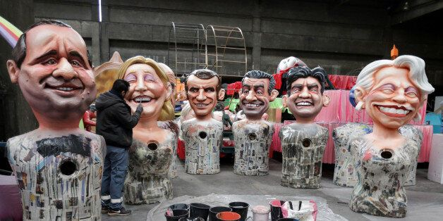 A worker puts the final touches to giant figures of French politicians (L-R) French President Francois...