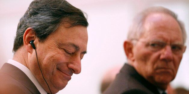 Mario Draghi, president of the European Central Bank (ECB), left, listens as Wolfgang Schaeuble, Germany's...
