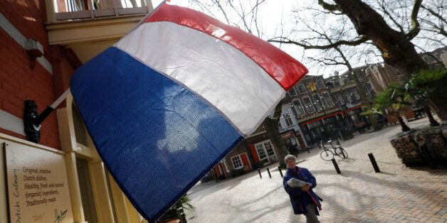 A woman walks past a national flag, the day before a general election, in Delft, Netherlands, March 14,...
