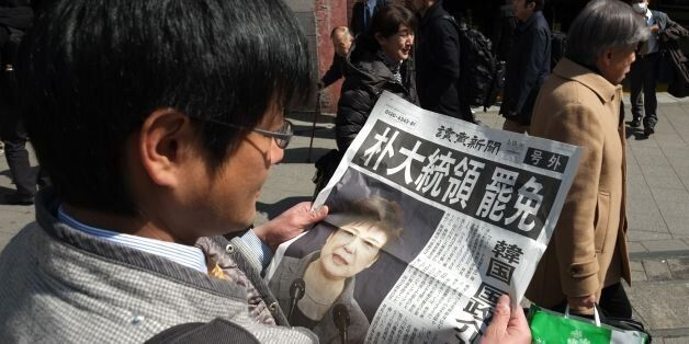 A man reads an extra edition of a Japanese major newspaper reporting on South Korean President Park Geun-hye's...