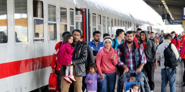 Migrants from Syria walk alomg a platform after arriving from Salzburg, Austria, at Schoenefeld railway...