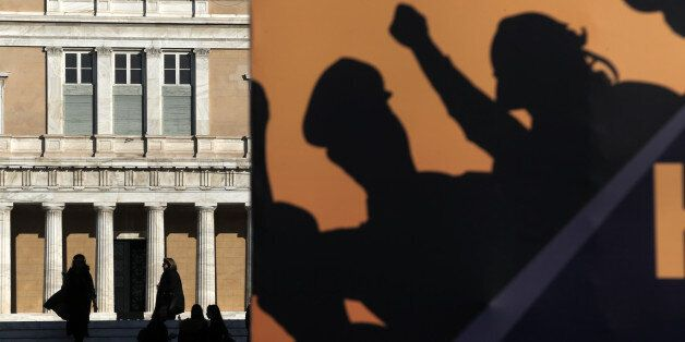 The Greek Parliament is seen behind a banner set by police officers at Syntagma square, during an anti-austerity...