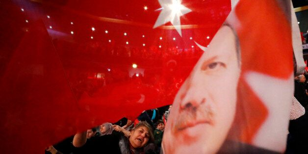 People wave with flags showing Turkish President Recep Tayyip Erdogan before Turkish Prime Minister Binali...