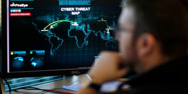 A FireEye information analyst works in front of a screen showing a near real-time map tracking cyber...