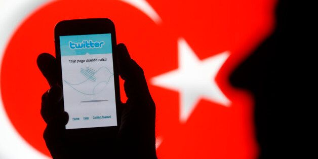 A holds holds a Samsung Galaxy S4 displaying a Twitter error message in front of Turkish national flag...