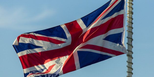 The Union Jack on a flag pole blows in the