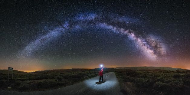 A young man on a road watching the Milky Way and lightning the road with a flash. Taken in A Veiga,