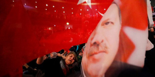 People wave with flags showing Turkish President Recep Tayyip Erdogan before Turkish Prime Minister Binali...