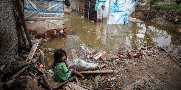 SULLANA, PERU - FEBRUARY 23: A girl sits near a flooded area after a heavy seasonal rainfall caused flood...