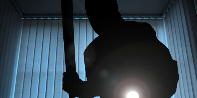 Burglar or intruder inside of a house or office with flashlight and baseball