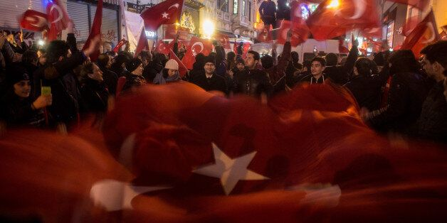 ISTANBUL, TURKEY - MARCH 12: Protesters hold a large Turkish flag as they sing songs and chant slogans...