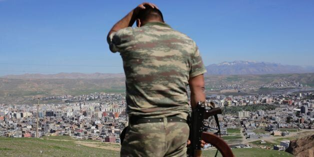 TOPSHOT - A Turkish soldier gestures while standing on the hill overlooking damaged buildings following...