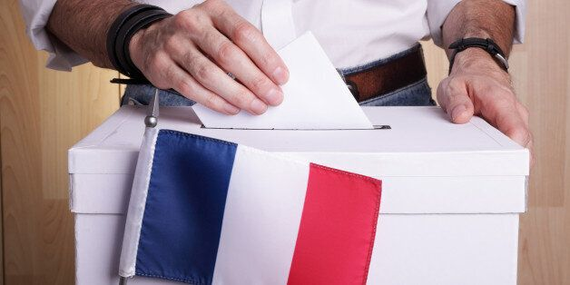 A man inserting a ballot to a ballot box. French flag in front of