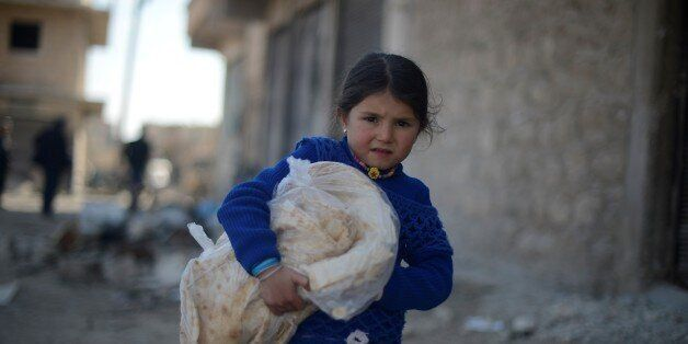 ALEPPO, SYRIA - MARCH 07: A Syrian girl carries a pile of bread, provided by the Foundation for Human...