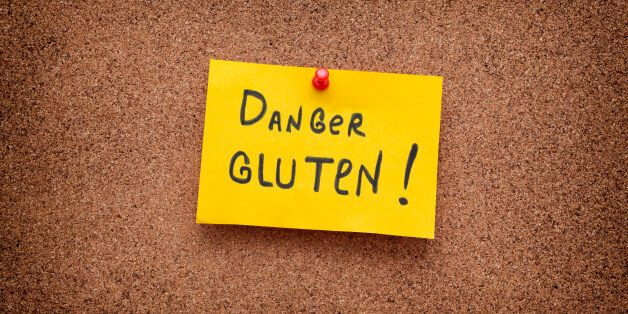 Paper note with the words Danger Gluten on cork board. Celiac Disease concept. Close up.