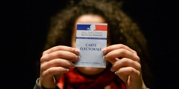 A woman holds her first electoral card, on March 19, 2017, in Besancon, eastern France. / AFP PHOTO /...