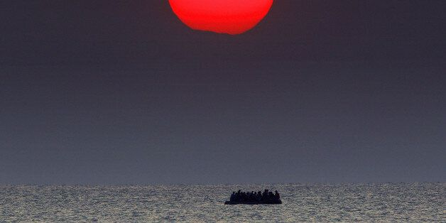 A red sun is seen over a dinghy overcrowded with Syrian refugees drifting in the Aegean sea between Turkey...