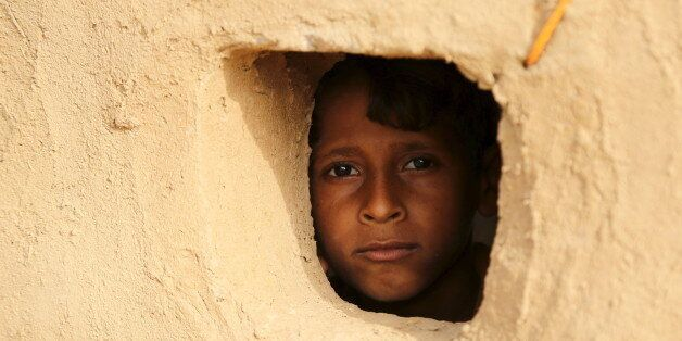 A boy looks from a window of his family's hut at the Shawqaba camp for internally displaced people who...