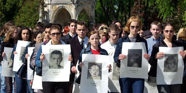 People hold portraits of children tortured and murdered by the Nazis inthe name of medicine during a...