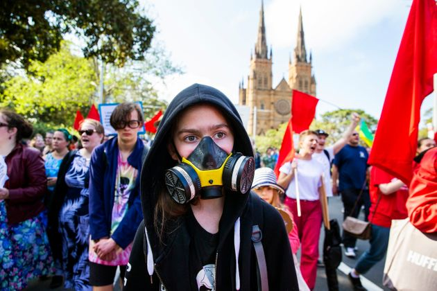 A girl wearing a gas mask marches along College Street during a climate strike rally on September 20,...