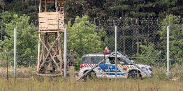 Kelebija, Serbia - September 10, 2016: Hungarian policemen watching the Serbia Hungarian border fence....