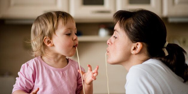 Mother and her little child sucking together spaghetti