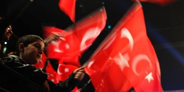 People wave Turkish flags during a campaigning event with the Turkish Prime Minister in Oberhausen, western...