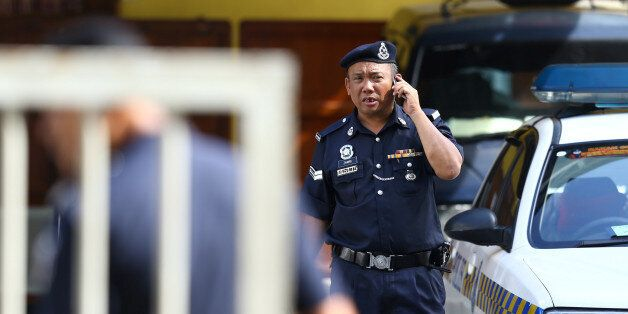 A police officer speaks on his mobile phone at the morgue at Kuala Lumpur General Hospital where Kim...